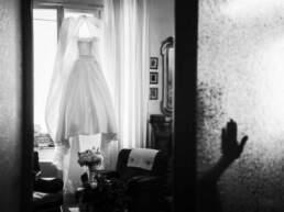 Una mano appoggiata sul vetro con l'abito della sposa di sfondo