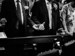 Le mani congiunte degli ospiti durante la preghiera in chiesa