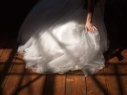 La mano della sposa mentre sistema il vestito