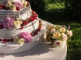 Dettaglio della torta nuziale e del bouquet di fiori