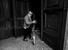 La perpetua pulisce l'ingresso della chiesa dai coriandoli